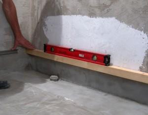 Выставить и закрепить планку на стене для укладки первого ряда плитки