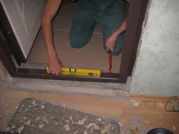 Проверка уровнем правильности установки дверной коробки